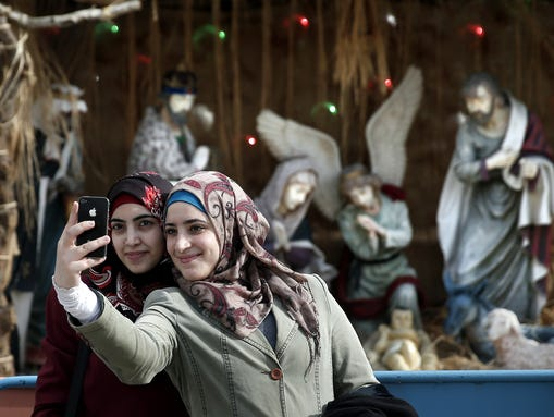 Muslim women take a selfie in front of the giant Christian