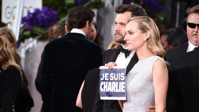 """Joshua Jackson and Diane Kruger pose with a sign reading """"Je Suis Charlie"""" at the Golden Globes."""