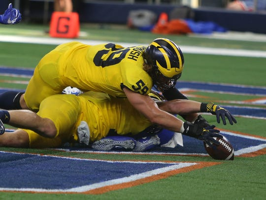 Michigan's Chase Winovich (bottom) forces a fumble