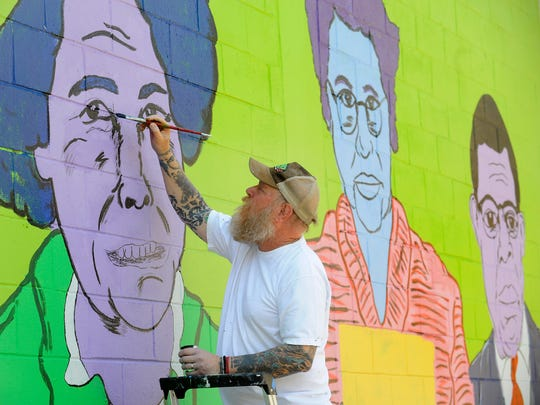 Tim Kerr paints a mural near the skateboard park in