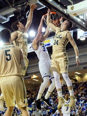 Delaware's Jacob Cushing dunks past William and Mary's Jack Whitman and David Cohn (right) in the first half at the Bob Carpenter Center Saturday.
