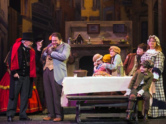 """Ebenezer Scrooge, portrayed by Mark Rutledge, converses with Bob Crachit (Jason Gerhard, second from left) as Tiny Tim (Russell Lindeman, right) observes the interaction during a scene in a special performance of """"A Christmas Carol"""" on the Lohrey Stage at Theatre Memphis on Tuesday. The play, in conjunction with Full Spectrum Theatre, was prepared specifically with a special needs audience in mind. The audience, for the approximately one-hour-long performance, was reserved for individuals with special needs, their friends, family and caretakers with modified audio and visual effects needs for a safe and judgment-free environment. For more show information, visit Theatre Memphis online at theatrememphis.org."""