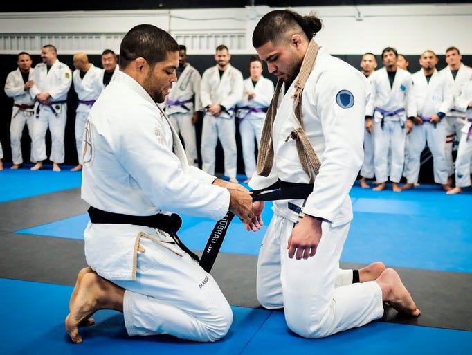 Mike Carbullido, right, receives his Brazilian jiu-jitsu