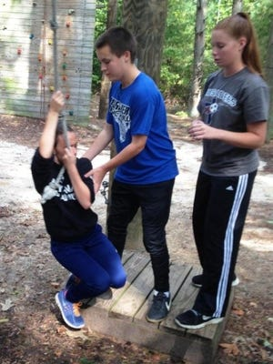 Cumberland Christian School students (from left) Jada Perez-Alvarado, Micah Jones and Veronica Fennimore participate in a swinging vine activity at Camp Edge.