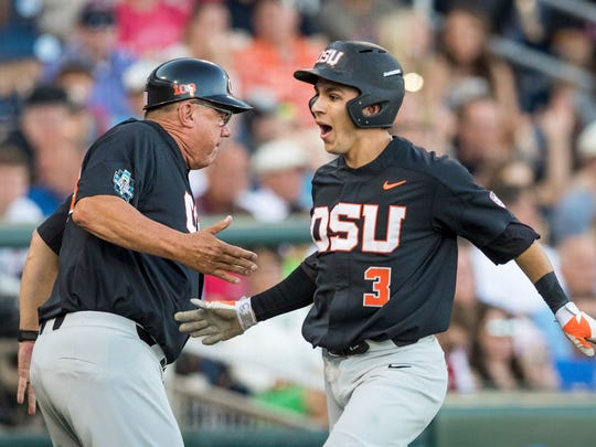 Oregon State's Nick Madrigal is greeted at home plate as he scores in the fifth inning of a College World Series baseball game against LSU.