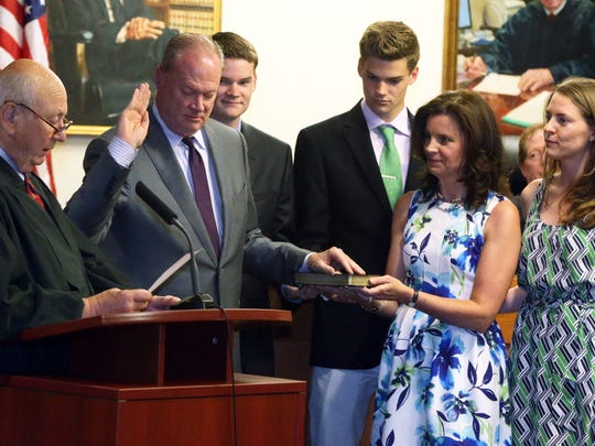 Peter J. Barnes III of Edison being sworn in as Middlesex County's newest Superior Court judge. He  was sworn in by retired Judge Robert Longhi (left)  at the Middlesex County Courthouse in New Brunswick on Thursday June 2, 2016 while his family watches (right)