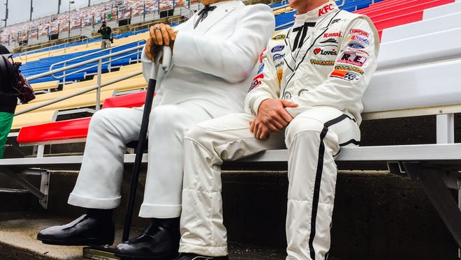 Driver Cole Whitt sits beside Col. Harland Sanders' statue Thursday at Kentucky Speedway.