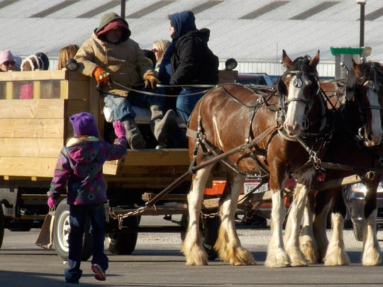FILE - Horse-drawn wagon rides are part of the fun at Mishicot's Christmas in the Village.
