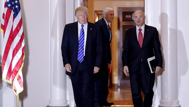 Then President-elect Donald Trump and Andy Puzder, chief executive of CKE Restaurants, walk from Trump National Golf Club Bedminster clubhouse in Bedminster, N.J., on Nov. 19, 2016. In the background is Vice President-elect Mike Pence.