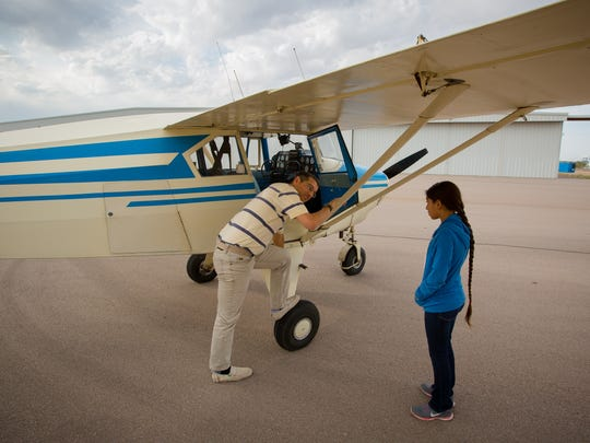 Pilot Chris Iriarte instructs 10-year-old Jarhec Arreola on the best way to climb into his 1957 Piper Tri-Pacer at the Las Cruces Airport as part of the Experimental Aircraft Association's Young Eagles event, May 14, 2016.