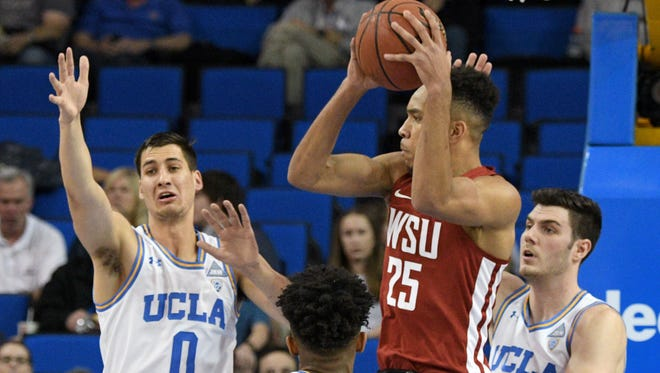 Washington State forward Arinze Chidom (25) looks to pass while being defended by UCLA's Alex Olesinski (0), Jaylen Hands (4) and Gyorgy Goloman, right, during the first half of Friday's game.
