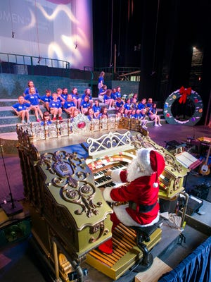 """Santa-clad artistic director Alex Gartner plays the newly refurbished vintage Robert Morton organ at the Saenger Theatre during the Pensacola Children's Chorus rehearsal on Wednesday, December 6, 2017.  The organ, that was installed as part of the Saenger's construction, will play a part in this year's """"Christmas on the Coast"""" performance."""