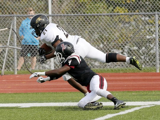 Corning's Ja'Ovian Fisher is tackled by Elmira's Autrale