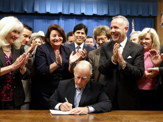 Gov. Jerry Brown receives applause from lawmakers as he signs a measure to place a $7.5 billion water plan on the November ballot Wednesday in Sacramento. The measure replaces an existing water bond that was  widely considered to costly.