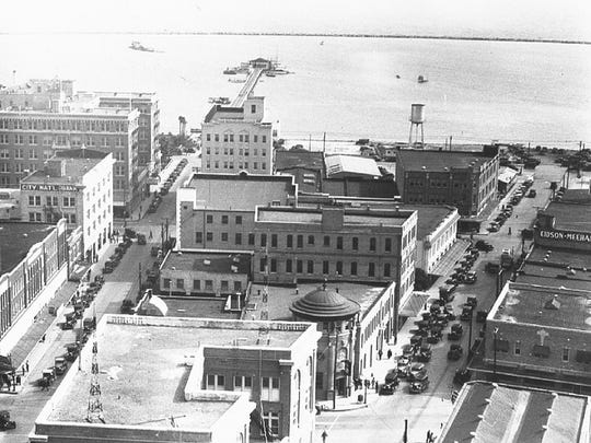 "A 1935 ""Doc"" McGregor photo shows Peoples Street to the left and Schatzel Street angling off to the right. Note the unusual shapes of the five major buildings along Schatzel, apparently designed to conform with the variant angle of the street."