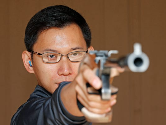 In this photo taken, Saturday, May 7, 2016, Jay Shi, an Olympics qualifier for the 2016 Rio Olympics in free pistol and air pistol, practices at a local shooting range in Phoenix. Shi has overcome damaged to his right eye to qualify for U.S. Olympic Team. He learned to shoot cross-eyed after injuring his eye as a child in his hometown of Beijing. (AP Photo/Ross D. Franklin)