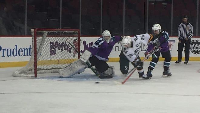 Passaic Valley/Cedar Grove junior Alex LoPresti, center, attempts to put the puck past Pascack Valley goalie Stephen Brennan.