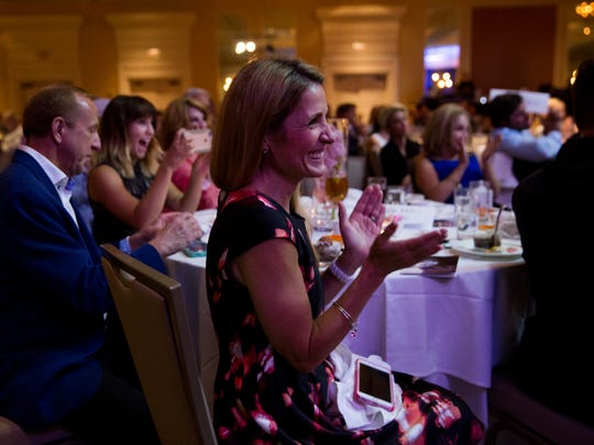 Barron Collier student counselor Melissa Hunter cheers after Barron Collier graduate Emily Browne receives the 2017 Winged Foot Scholar Athlete Award during the Winged Foot Scholarship Awards Banquet at the Naples Grand Beach Resort Thursday, May 25, 2017 in Naples.