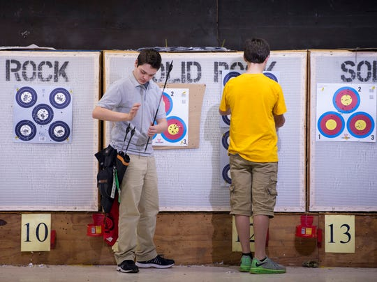 Blayne Sands, 14, collects his arrows from the round targets at Black Hawk Bowhunters in Newburgh, Ind., in November.