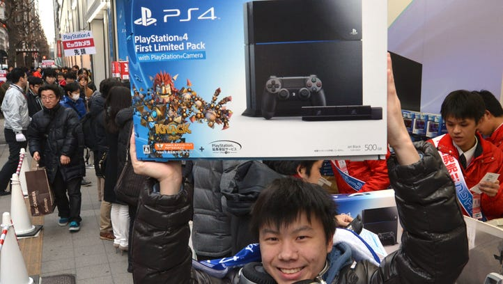 A customer reacts after buying Sony's PlayStation 4