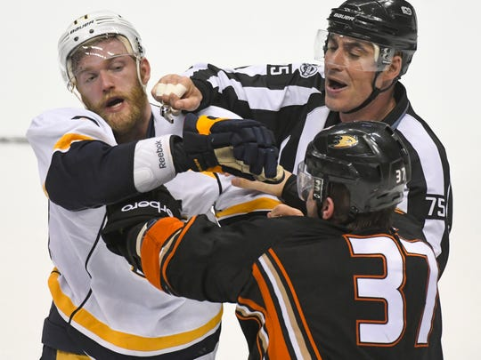 A referee tries to break up a fight between Nashville Predators defenseman Mattias Ekholm (14) and Anaheim Ducks left wing Nick Ritchie (37) during the closing seconds of Game 5 of the NHL Western Conference finals at Honda Center in Anaheim, Calif.