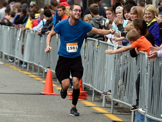 Chris Wagler of Odon is greeted by friends and family as he approaches the finish line of the Evansville Half Marathon on Riverside Dr., in Evansville Saturday.