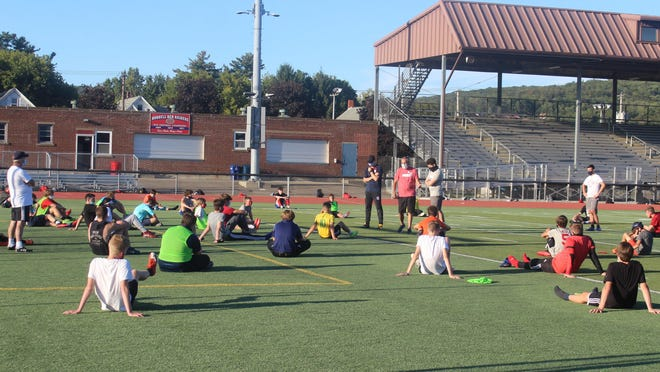 Head coach Jim Tobin talks to the boys soccer team at the end of practice on Monday evening.