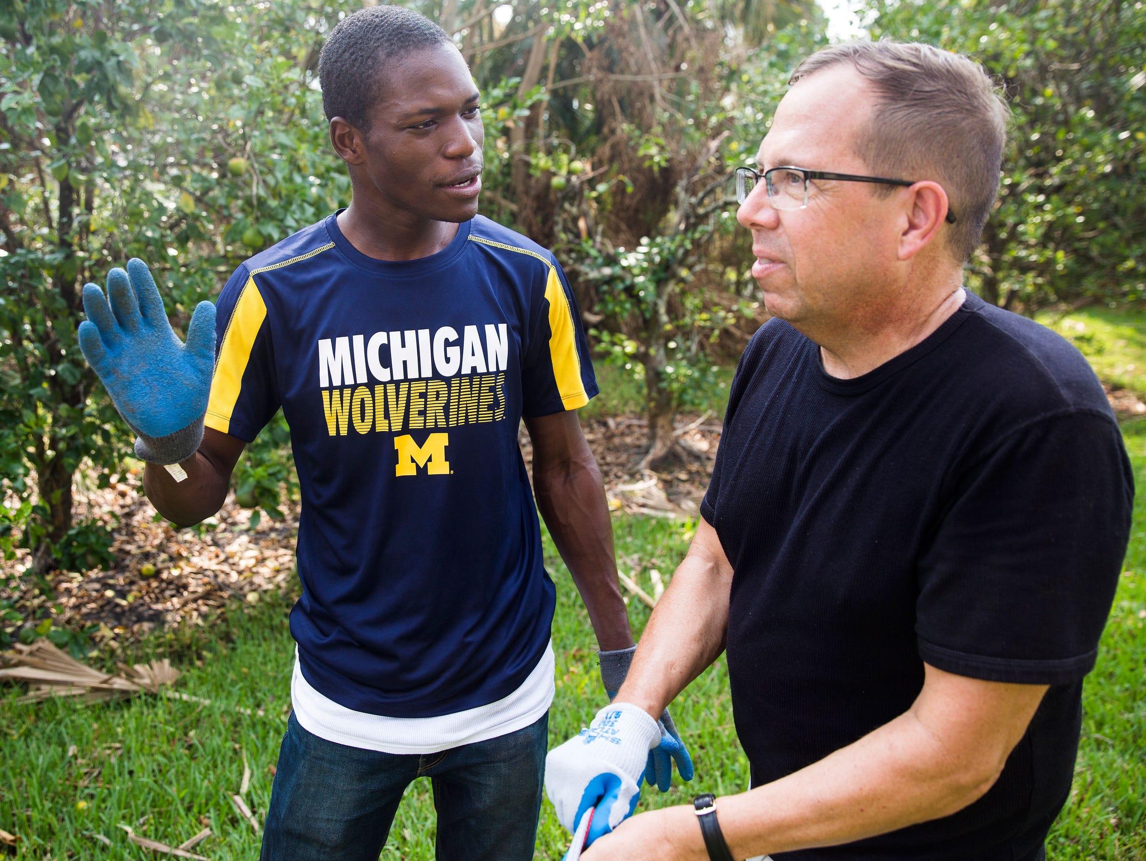 Nehemy Antoine, left, and pastor Eric Hausler chat
