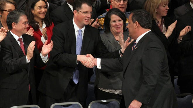 Gov. Chris Christie (right) shakes hands with his then-chief of staff Kevin O'Dowd in this January 2014 photograph. O'Dowd was the governor's choice to become the next state attorney general but the nomination did not move forward. Acting Attorney General John Hoffman applauds at the Trenton War Memorial. (Staff photo/Thomas P. Costello)