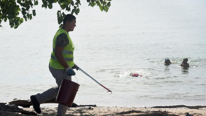 Preston Lefere picks up trash along the beach at Sterling State Park. Lefere was part of a 4-week summer program that provides work experience for individuals with disabilities who are age 18 or older. The program is a collaboration between the Department of Natural Resources, Michigan Rehabilitation Services and the Monroe Center for Independent Living.