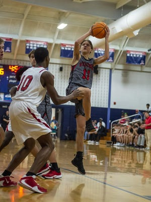 Wheatmore's Gavin Dennis shoots against Providence Grove's Jonathan Foust last season. The teams played Tuesday night, with Providence Grove taking a 47-42 win. [PJ Ward-Brown for The Courier-Tribune]