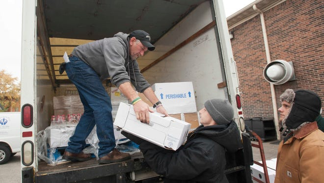 Kentucky Harvest, which transports donated food to about 100 charities in the Metro area, had a truckload of groceries delivered to The Healing Place on Market Street. Earl Harper unloads the truck as he hands some turkeys to fellow Healing Place resident Jesse Richardson as (resident) Ryan Dattilo, right, waits next in line to help. 13 November 2014