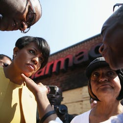 BALTIMORE, MD - MAY 07: Gita Stevenson (R), a volunteer at the Meditation Museum in Silver Spring, Maryland, touches the chin of Mayor Stephanie Rawlings-Blake (2nd L) after a news conference in front of the burned CVS in the Sandtown neighborhood May 7, 2015 in Baltimore, Maryland. Community leaders joined the mayor to kick off the One Baltimore campaign, a public-private initiative to support efforts to rebuild communities and neighborhoods after the riot that was caused by the death of Freddie Gray. (Photo by Alex Wong/Getty Images) *** BESTPIX *** ORG XMIT: 553072105 ORIG FILE ID: 472433684