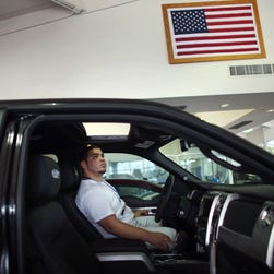 Roger Rodriguez looks at a F-150 pickup on the showroom floor at at a Ford dealer operated by AutoNation in North Miami, Fla., in this 2003 file photo