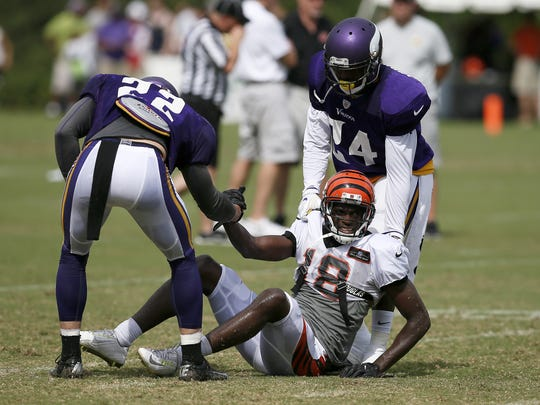 Cincinnati Bengals wide receiver A.J. Green is helped up by Minnesota Vikings free safety Harrison Smith and cornerback Captain Munnerlyn after tumbling on a play during training camp on Aug. 10.