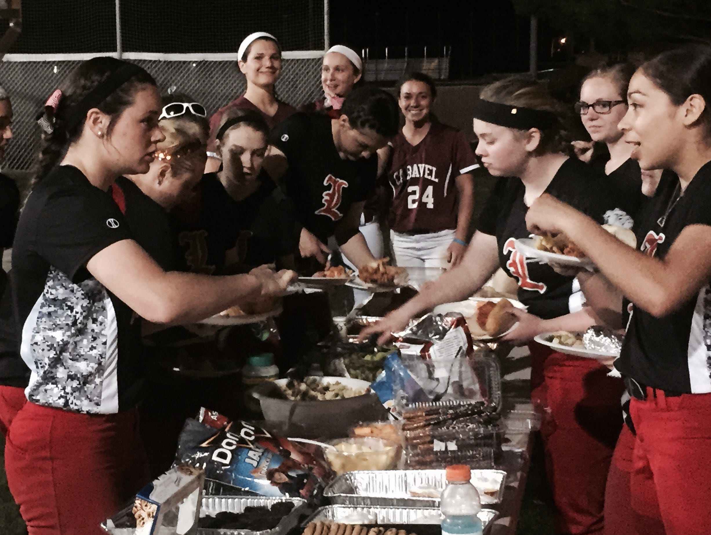 Laurel and Caravel players enjoy a postgame cookout at Caravel following Laurel's 1-0 softball victory on Friday night.