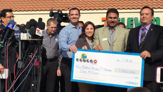 From right, California State Lottery Director Hugo Lopez presents a $1 million check to 7-Eleven owner Balbir Atwal in front of Atwal's store on Thursday, Jan. 14, 2016.