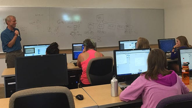 Chris Wilcox, left, teaches young women during a Girls Who Code summer programming camp.