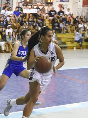 Kali Benavente (3) of the Academy of Our Lady of Guam Cougars takes the ball down court against the Notre Dame Roylas.