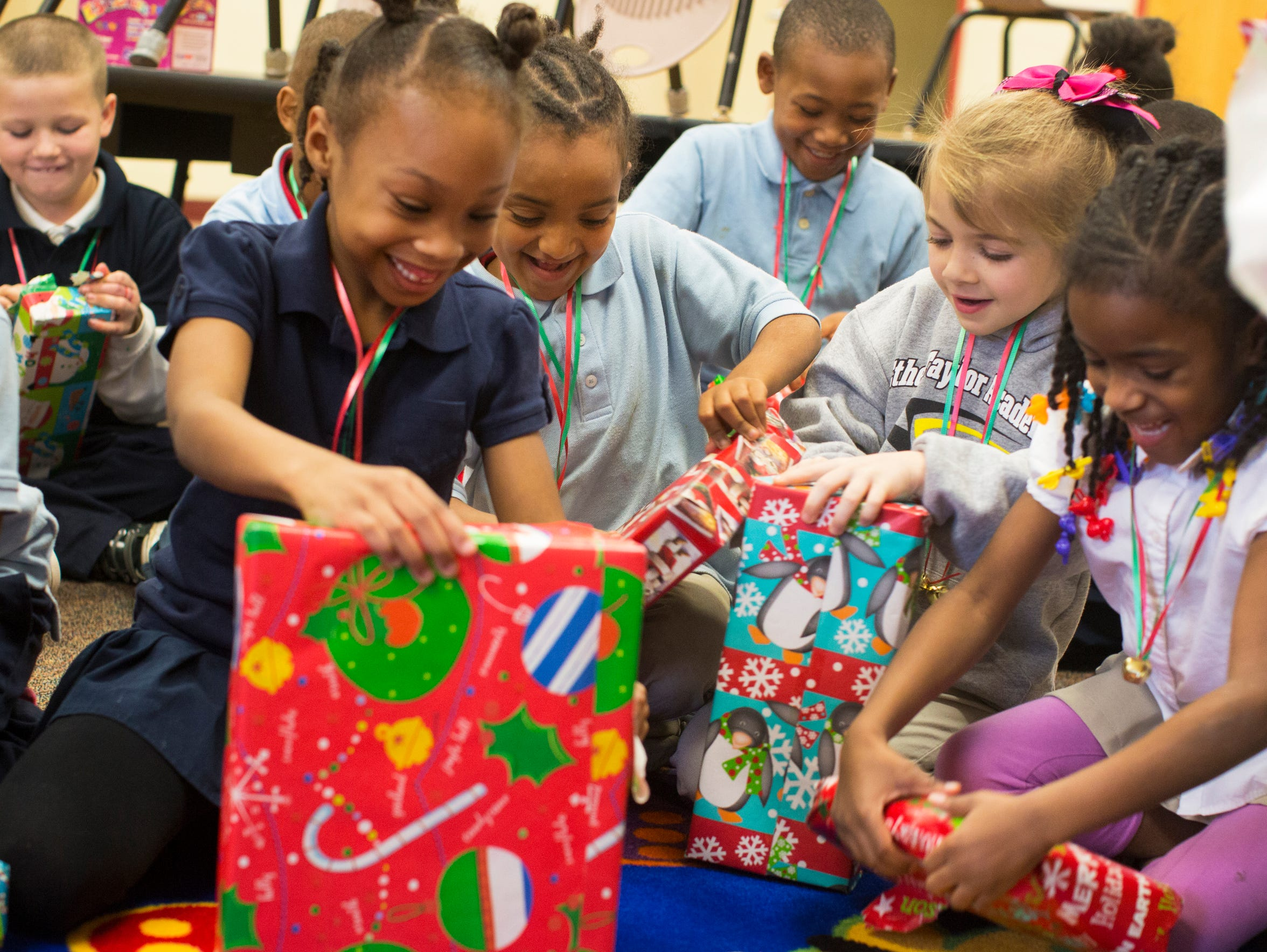 First-graders tear into their gifts, courtesy of Fidelity,