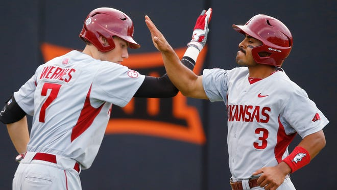 Arkansas' Michael Bernal (3) celebrates with teammate Bobby Wernes after scoring on a hit by Joe Serrano in the fifth inning of the Stillwater Regional  title game against St. John's in Stillwater, Okla., on Sunday night. Arkansas won 4-3 to advance to the Super Regional round.