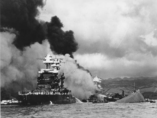Torpedoed and bombed by the Japanese, the battleship USS West Virginia begins to sink after suffering heavy damage, center, while the USS Maryland, left, is still afloat in Pearl Harbor.  The capsized USS Oklahoma is at right.