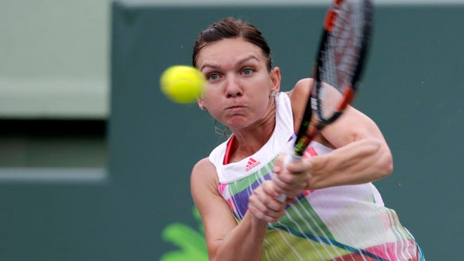 Simona Halep, of Romania, returns to Timea Bacsinszky during their match at the Miami Open tennis tournament, Tuesday, March 29, 2016, in Key Biscayne, Fla.  (AP Photo/Lynne Sladky)
