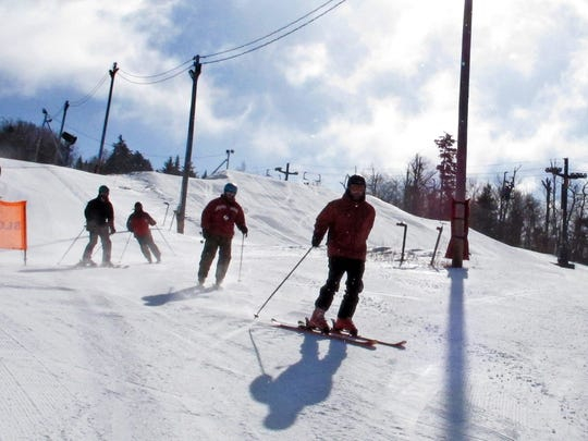 Military veterans, who suffer post-traumatic stress disorder, ski together at Bolton Valley Resort in Bolton, Vt, Thursday Feb. 18, 2016.  A group of service members of the Gulf, Iraq and Vietnam wars say the weekly gatherings through the Vermont Adaptive Ski & Sport programs help get them out of the house, connect with other people and take their mind off of their post-traumatic symptoms.