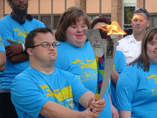 Justin Reagan holds the Special Olympics torch during