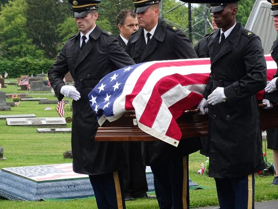 A military honor guard lifts the casket of John Kovach