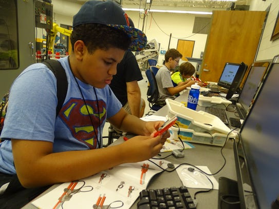 Mychael Gamble, 12, of Fremont, works on building a