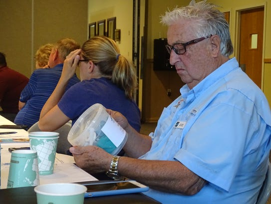 Len Partin reviews a test kit used by Rotary Club District