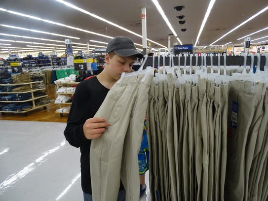 Logan Pollick, 12, searches for pants for the school