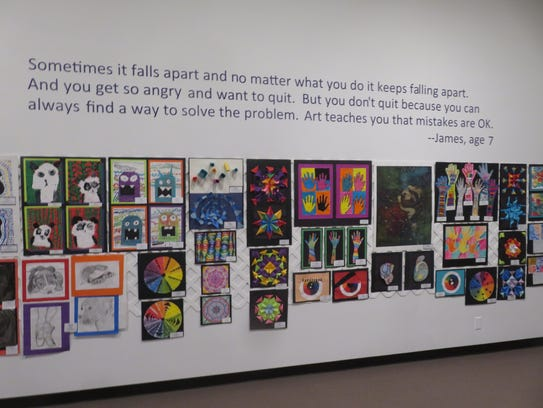 A wall of art at the All School Exhibition, accompanied
